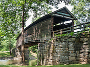 "Humpback Covered Bridge, built in 1857, is the oldest remaining covered bridge in the state of Virginia. Humpback Bridge is one of the few remaining covered bridges in the USA built higher in the middle than on either end (with a humpback 4 feet or 1.2 meters high). The bridge spans 109 feet (33 m) across Dunlap Creek (a tributary of Jackson River), near Covington, Virginia. Covered wooden bridges averaged ten times the lifespan of uncovered ones. Sometimes referred to as ""kissing bridges"" during the modest era of the late 1800s, covered bridges allowed horse and buggy passengers kissing privacy. Two former non-covered bridges here (built in the 1820s and 1838) were destroyed by floods, and a third bridge collapsed in 1856 due to heavy use and weathering. All three bridges were a part of the James River and Kanawha Turnpike, a heavily traveled mountain road that connected the Shenandoah Valley with the Alleghany Mountains and westwards. The decking, unlike houses and other structures, could not be painted to prevent deterioration, as the traffic from horses and wagons would quickly remove any available paints of the era. The Humpback Covered Bridge was used from 1857 to 1929, when a steel truss bridge was built for US Highway 60 immediately to the north. The bridge was listed in the National Register of Historic Places in 1969. The bridge retains most of its original 1857 hand-hewn white oak and hickory support timbers and decking, but most of the walls and roofing have been replaced several times. The supports incorporate a unique curved multiple kingpost-truss system that is not found in any other surviving wooden bridge in the USA. The bridge is a unique design not duplicated anywhere else. How to reach Humpback Bridge: Take Exit number 10 off of Interstate 64 in Virginia and follow signs, 1 mile east. It is 3 miles west of Covington, Virginia adjacent to U.S. Highway 60 off Rumsey Road (SR 600)."