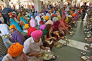 Tradition wants that everybody sits on the floor in rows next to each other. Volunteers (sewadars) walk continuously along the isles serving foods and water from metal buckets.