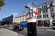 A City of London dragon boundary mark bollard on the border of Tower Hamlets as traffic passes on Lower Thames Street on September 06, 2018. The dragon boundary marks are cast iron statues of dragons on metal or stone plinths that mark the boundaries of the City of London painted silver, with details of the dragon wings and tongue picked out in red.