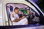 "02 OCTOBER 2009 -- BANGKOK, THAILAND:  ORACHUN, a medic and shift supervisor with Poh Teck Tung, does paperwork in his ambulance between calls. The 1,000 plus volunteers of the Poh Teck Tung Foundation are really Bangkok's first responders. Famous because they pick up the dead bodies after murders, traffic accidents, suicides and other unplanned, often violent deaths, they really do much more. Their medics respond to medical emergencies, from minor bumps and scrapes to major trauma. Their technicians respond to building collapses and traffic accidents with heavy equipment and the ""Jaws of Life"" and their divers respond to accidents in the rivers and khlongs of Bangkok. The organization was founded by Chinese immigrants in Bangkok in 1909. Their efforts include a hospital, college tuition for the poor and tsunami relief.   PHOTO BY JACK KURTZ"