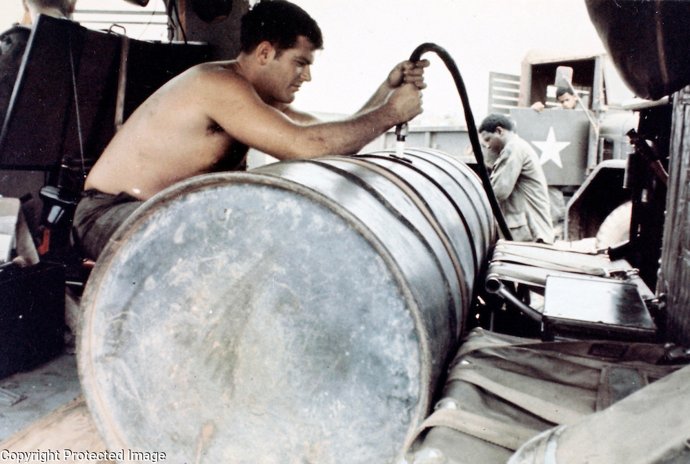 SP4 Gerry Miller (Alton, Ill), (foreground), and SP4 Frank W. Davis (Elizabeth, N.J.), both members of the 184th Chemical Co, 1st Cavalry Division (Airmobile), use compressed air to fill a 110 gallon tank mounted on a UH-1B helicopter. 20, March 1970
