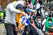 London, United Kingdom, May 22, 2021: Protester set fire to a Israeli flag as they gather near to the Israeli embassy in Kensington, central London on Saturday, May 22, 2021. A march in solidarity with the people of Palestine following a ceasefire agreement between Hamas and Israel. Among the groups in attendance were branches of the National Education Union, the Palestine Solidarity Campaign, Palestine Action and Stop The War Coalition. (Photo by Vudi Xhymshiti/VXP)