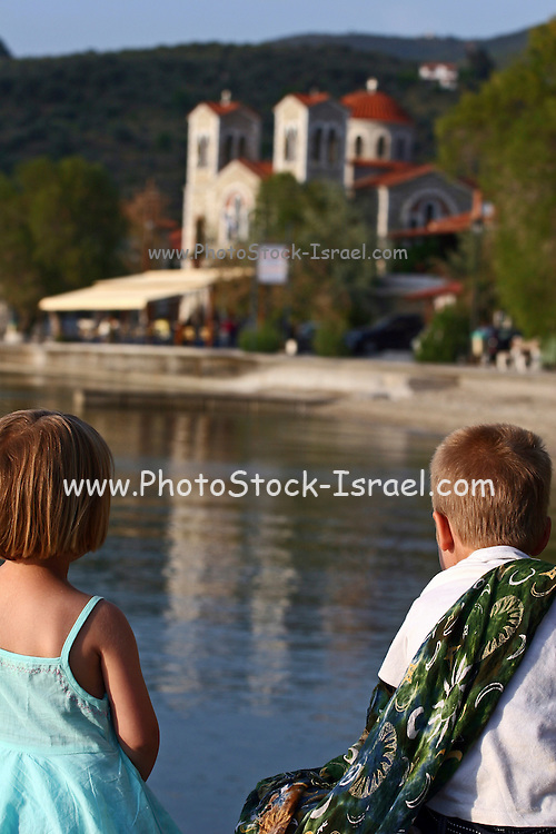 Greece, Thessaly, Agia Kiriaki, Two children a boy and a girl looking over the bay at the large building of the church