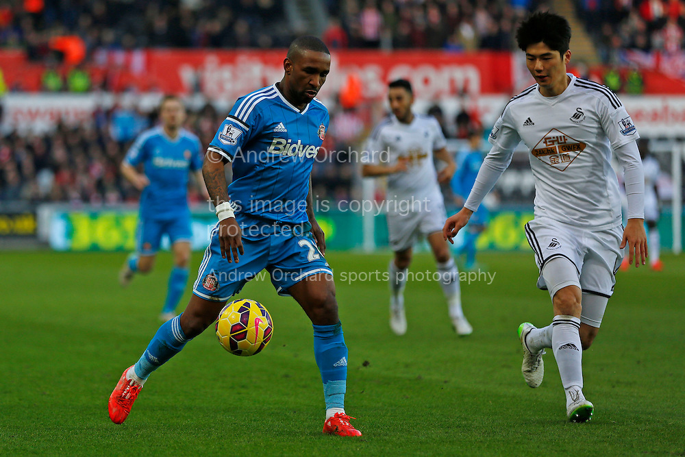 Jermain Defoe of Sunderland controls the ball under the watch of Ki Sung-Yueng of Swansea.<br /> Barclays Premier League match, Swansea City v Sunderland at the Liberty stadium in Swansea, South Wales on Saturday 7th Feb 2015.<br /> pic by Mark Hawkins, Andrew Orchard sports photography.