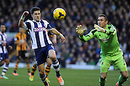 Shane Long of West Brom looks to beat Hull goalkeeper Alan McGregor (r). Barclays Premier league, West Bromwich Albion v Hull city at the Hawthorns in West Bromwich, England on Saturday 21st Dec 2013. pic by Andrew Orchard, Andrew Orchard sports photography.