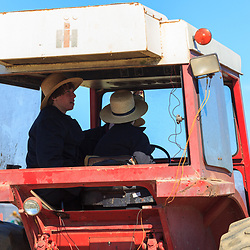 Gordonville, PA, USA - March 10, 2012: Two Amish youths sit in a farm tractor at a public mud sale to benefit the Gordonville Volunteer Fire Company in Lancaster County, PA.