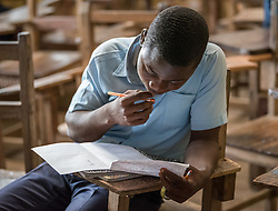 4 November 2019, Montserrado, Liberia: A male student reads his study materials during recess. Started as a school for internally displaced children during the First Liberian Civil War, Mother Tegeste Stewart Apostolic Pentecostal Mission School in Montserrado county currently teaches 486 students from kindergarten up through 12th grade.