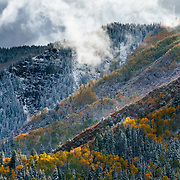 The sun breaks out of storm clouds to sidelight mountain ridges in White River National Forest near Carbondale, Colorado.