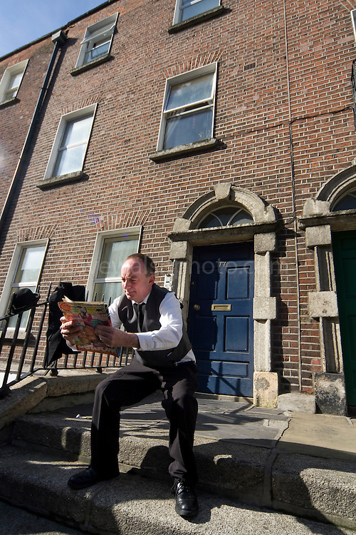 """Editorial Use Only. Bloomsday June  16th 2008, Dublin. Actor Paul O'Hanrahan from Balloonatics theatre company performs the """"Calypso"""" chapter from  James Joyce novel Ulysses around Eccles St. and Dorset Street. ..In this photo, Bloom is reading while sitting on the """"jakes"""" or toilet."""