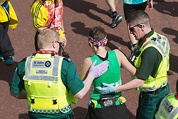 © Licensed to London News Pictures. 21/04/2013. London, England. Picture: An exhaused runner receives help from St John Ambulance. Celebrity Runners and Fun Runners finish the Virgin London Marathon 2013 race in the Mall, London. Many wore black ribbons to pay their respect for those who died or were injured in the Boston Marathon. Photo credit: Bettina Strenske/LNP