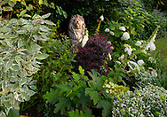 A lion sculpture surrounded by Hydrangea and a variety of plants in a small private garden in West London.