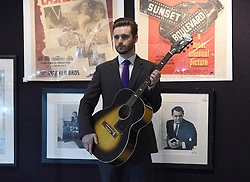 A staff member holds a guitar once owned by Jimi Hendrix on display at the Entertainment Memorabilia Sale at Bonhams in Knightsbridge, London.