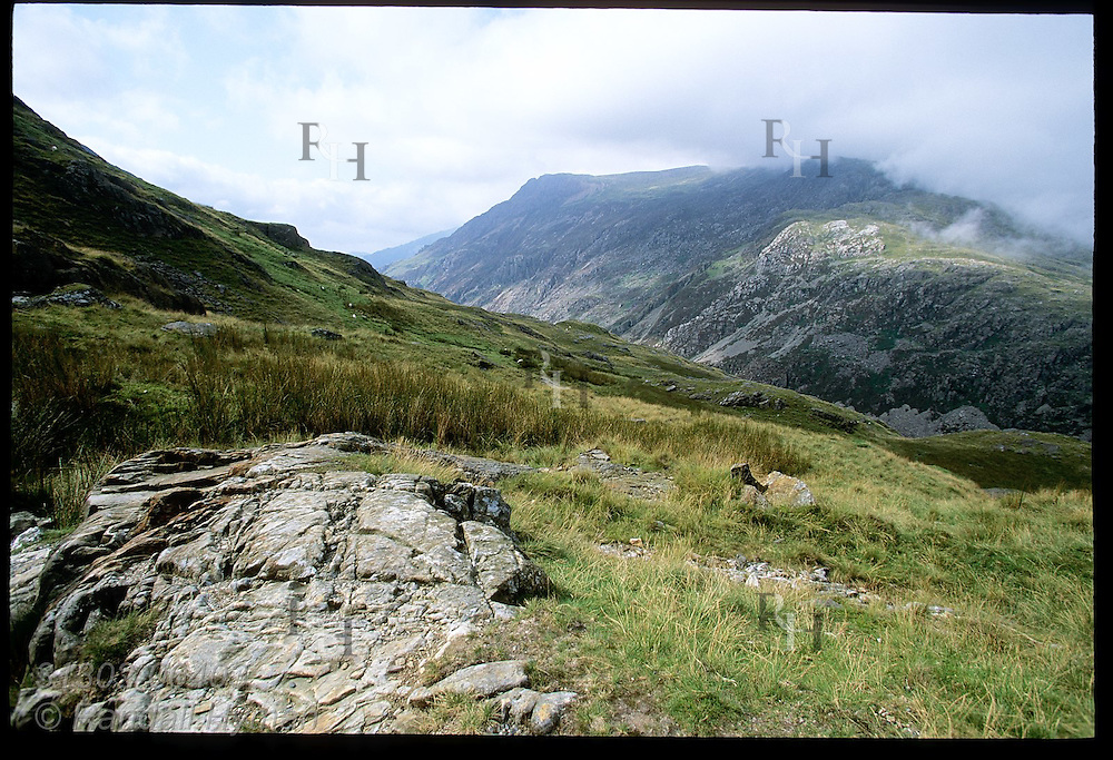 Rock outcrop punctuates grassy alpine field overlooking distant valley in Snowdonia National Park, Wales.
