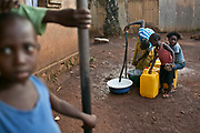 Residents fetch water from a faucet that was installed by the city government in Bangui. Neighbors pay 15 CFA (about three US cents) per gallon of water, and a family of four or five could spend between 100 to 500 CFA (about 20 cents to 1 US Dollar) a day on water depending on the quantity and the availability of the free, ground water. The faucets are run by the Societe Centralfricaine des Eaux, a government agency.