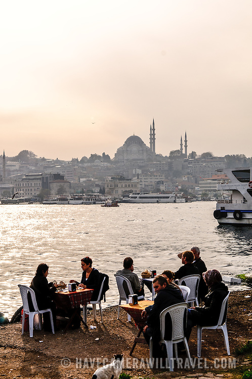 Diners at a fish restaurant next ot the Karakoy Fish Market in Istanbul near the Galata Bridge. In the distance, across the Golden Horn, is the Suleymaniye Mosque on the skyline.