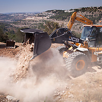 Here Israeli machinery is at work building the Separation Barrier in the West Bank, near Beit Jala. <br /> <br /> 85% of the barrier's planned route runs through the West Bank, mainly in areas where there are Israeli settlements and industrial zones. By July 2012, construction of the barrier was 62% complete. It left some 3% of the West Bank territory cut off, west of the barrier. Completed as planned, the barrier will isolate an additional area of more than 6% of West Bank lands on the Israeli side. Construction of the barrier in the West Bank gravely violates the rights of Palestinians in the areas affected, restricting their access to their lands, crucial services and relatives on the other side of the barrier. The barrier also prevents any possibility of economic development.