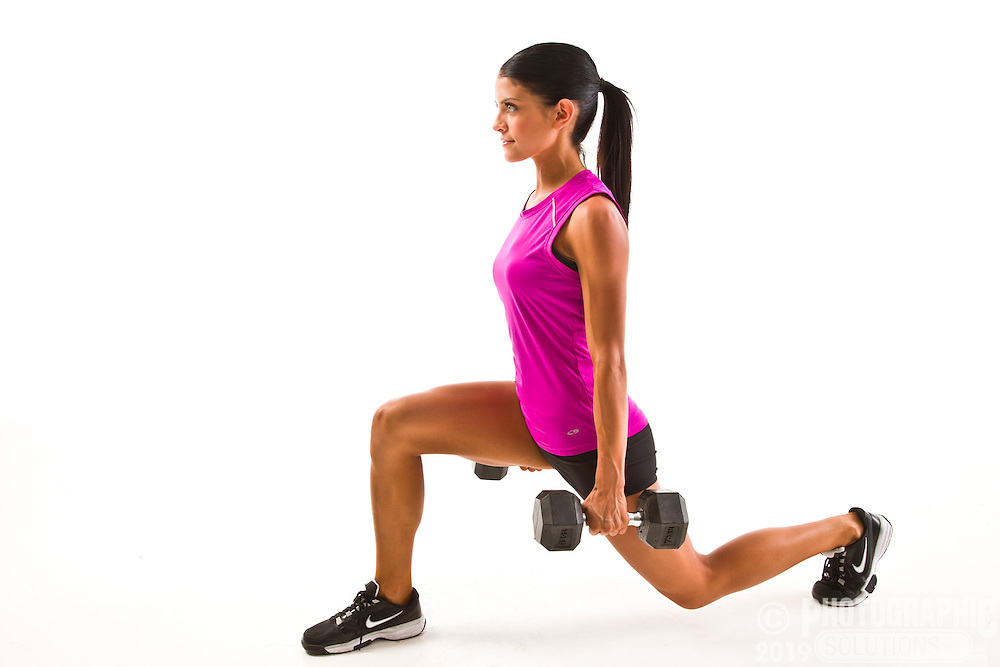 Fitness shots in studio, a woman doing lunges with weights