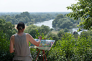 A male artist painting a picture of the Thames River on the 25th July 2019 in Richmond in the United Kingdom.