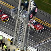 Ryan Reed (16) crosses the finish line ahead of Chris Buescher (60) to win the Alert Today Florida 300 XFinity Series race at Daytona International Speedway on Saturday, February 21, 2015 in Daytona Beach, Florida.  (AP Photo/Alex Menendez)