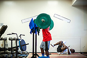 """BEAUFORT, SC - JULY 14: CJ Cummings, right, stretches his legs while the other students work out at the weight lifting facility at the Beaufort Middle School on July 14, 2014 in Beaufort, South Carolina. A former U.S. Olympic coach has called Cummings """"the best weightlifter this country has ever seen."""" (Photo by Stephen B. Morton for The Washington Post)"""