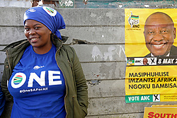 Wednesday 8th May 2019.<br /> Monwabisi Park, Harare,<br /> Khayelitsha, Cape Town, <br /> Western Cape, <br /> South Africa.<br /> <br /> SOUTH AFRICAN GENERAL ELECTIONS 2019!<br /> <br /> SOUTH AFRICAN PROVINCIAL AND NATIONAL ELECTIONS 2019! <br /> <br /> A DA supporter wears DA colours as she stands near an ANC elections poster outside the voting station at Monwabisi Park, Harare in Khayelitsha near Cape Town, Western Cape, South Africa.<br /> <br /> Registered South African Voters head to the various IEC (Independent Electoral Commission) Voting Stations where they are registered to vote as they cast their votes and take part in voting and other activities on Voting Day 8th May 2019 during the South African General Elections 2019. Voters from across the nation stood in queue's along with many others to vote in the Provincial and National Elections being held in South Africa on Wednesday 8th May 2019.   <br />  <br /> Copyright © Mark Wessels. All Rights Reserved. No Usage Without Permission.<br /> <br /> PICTURE: MARK WESSELS. 08/05/2019.<br /> +27 (0)61 547 2729.<br /> mark@sevenbang.com<br /> studioseven@mweb.co.za<br /> www.markwesselsphoto.com