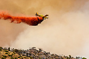22 JUNE 2005 - CAVE CREEK, AZ:   A plane drops retardant on the Cave Creek Complex, a large wild fire which burned northeast of Phoenix. The Cave Creek Complex fire was the third largest wildfire in the state of Arizona to date, after the Rodeo-Chediski fire and Wallow Fire. The fire started on June 21, 2005 by a lightning strike during a monsoon storm and burned 243,950 acres (987.2 km2).   PHOTO BY JACK KURTZ