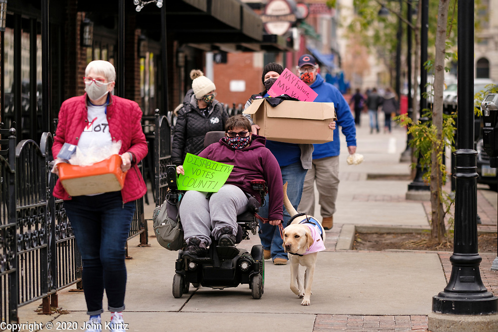 """29 OCTOBER 2020 - DES MOINES, IOWA: Handicapped voters participate in the """"Roll and Stroll to the Polls,"""" sponsored by the Central Iowa Center for Independent Living and CanvassHat near the Polk County Auditor's Office in Des Moines. There have been long lines for early voting all month. According to the Polk County Auditor's Office, as of October 27, 120,752 ballots have been returned of the 144,028 ballots requested for a return rate of 83.84 percent. Iowa starts counting early ballots the morning of Nov. 3.     PHOTO BY JACK KURTZ"""