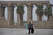 A young Egyptian family walk away from the ancient Egyptian columns of Luxor Temple, Luxor, Nile Valley, Egypt.  The temple behind was built by Amenhotep III, completed by Tutankhamun then added to by Rameses II. Towards the rear is a granite shrine dedicated to Alexander the Great and in another part, was a Roman encampment. The temple has been in almost continuous use as a place of worship right up to the present day.