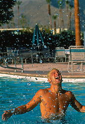Man splashing in a swimming pool in Palm Springs, CA
