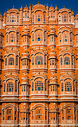 """Hawa Mahal (""""Palace of Winds"""" or """"Palace of the Breeze""""), is a palace in Jaipur, India. It was built in 1798 by Maharaja Sawai Pratap Singh, and designed by Lal Chand Ustad in the form of the crown of Krishna, the Hindu god. Its unique five-storey exterior is also akin to the honeycomb of the beehive with its 953 small windows called jharokhas that are decorated with intricate latticework. The original intention of the lattice was to allow royal ladies to observe everyday life in the street below without being seen, since they had to observe strict """"purdah"""" (face cover). Besides this, the lattice also provides cool air caused by the Venturi effect (doctor breeze) through the intricate pattern and thereby air conditioning the whole area during the high temperatures in summers. Built of red and pink sandstone, the palace is situated on the main thoroughfare in the heart of Jaipur's business centre. It forms part of the City Palace, and extends to the Zenana or women's chambers, the chambers of the harem. It is particularly striking when viewed early in the morning, lit with the golden light of sunrise."""