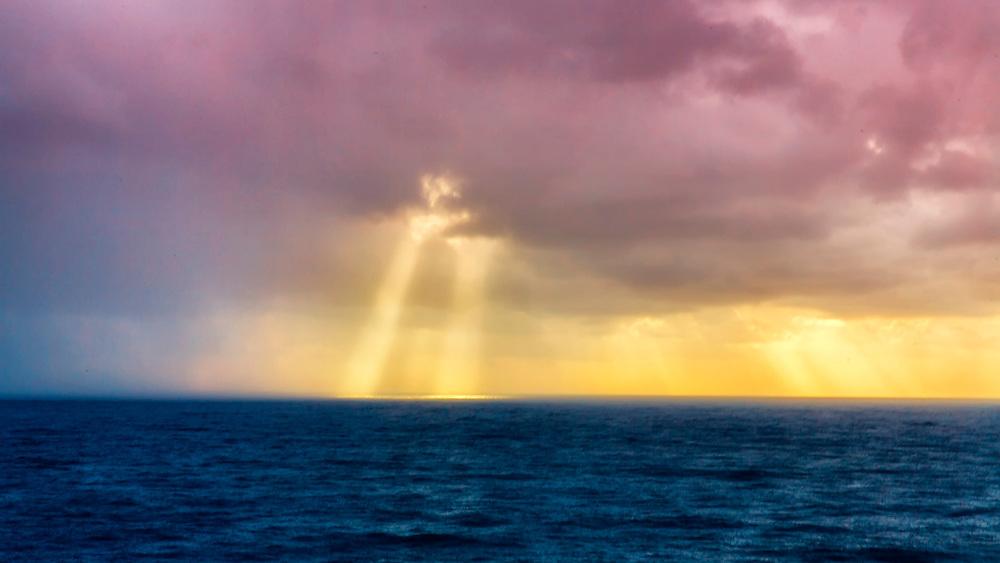 Morning Sunrise Light Peeks Through Pastel Skies Over The Deep Blue Ocean Waters Of Hawaii