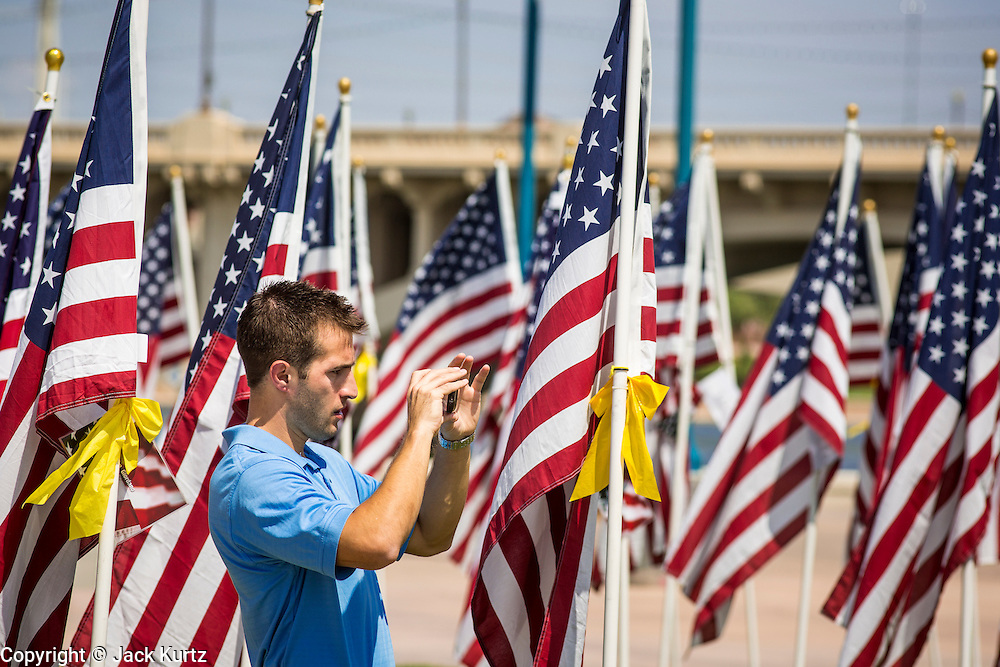 10 SEPTEMBER 2012 - TEMPE, AZ:  A man photographs American flags in  the Healing Field in Tempe, AZ, Monday. The Exchange Club of Tempe and the city of Tempe are hosting the 9th Annual Healing Field display. The annual event posts three thousand American flags in the Tempe Beach Park. The flags are 3?X5?  and stand 8? tall. The display is a tribute to those who died in the terrorist attacks of September 11, 2001. Nearly 3,000 people were killed when terrorists affiliated Al-Qaeda crashed commercial airliners into the World Trade Center in New York, the Pentagon in Arlington, VA, and a field in Ohio.   PHOTO BY JACK KURTZ
