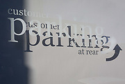 A detail of sign lettering and shadows telling cusomers of a local business that customer parking is at the rear of the premises, on 7th November 2019, in Surbiton, London, England.
