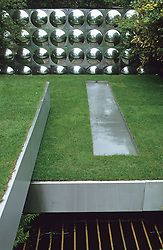 Stainless steel 'trays' of lawn creating different levels. Steel rill dropping down to square ponds below. Workshop clad with aluminium disks. Design Diarmuid Gavin