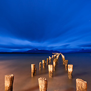 Wooden pillars of an old pier stand motionless against a turbulent sky and sea shore turned smooth in a 2 minute long exposure. Street lights create a redish hue against the blue dusk in Puerto Natales, Patagonia, Chile.
