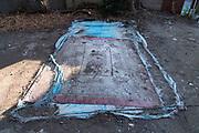 damaged blue tarp and old carpet on dirt ground