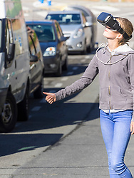 Girl using virtual reality headset while hitchhiking on road
