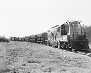 """Ackroyd 06955-11. """"Batten, Barton, Durstine & Osburn. Logs at Northern Pacific side track, Vancouver, Washington. June 25, 1956"""" side and front view of logging train, men on the engine."""