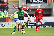 Aberdeen's Scott Brown (8) and Kevin Nisbet (15) of Hibernian battles for possession, tussles, tackles, challenges, during the Cinch Scottish Premiership match between Aberdeen and Hibernian at Pittodrie Stadium, Aberdeen, Scotland on 23 October 2021.