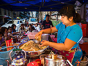 "06 NOVEMBER 2015 - YANGON, MYANMAR: A woman makes a batch of noodles for a customer at her street food stall in Yangon. Some economists think Myanmar's informal economy is larger than the formal economy. Many people are self employed in cash only businesses like street food, occasional labor and day work, selling betel, or working out of portable street stalls, doing things like luggage repair. Despite reforms in Myanmar and the expansion of the economy, most people live on the informal economy. During a press conference this week, Burmese opposition leader Aung San Suu Kyi said, ""a great majority of our people remain as poor as ever.""   PHOTO BY JACK KURTZ"