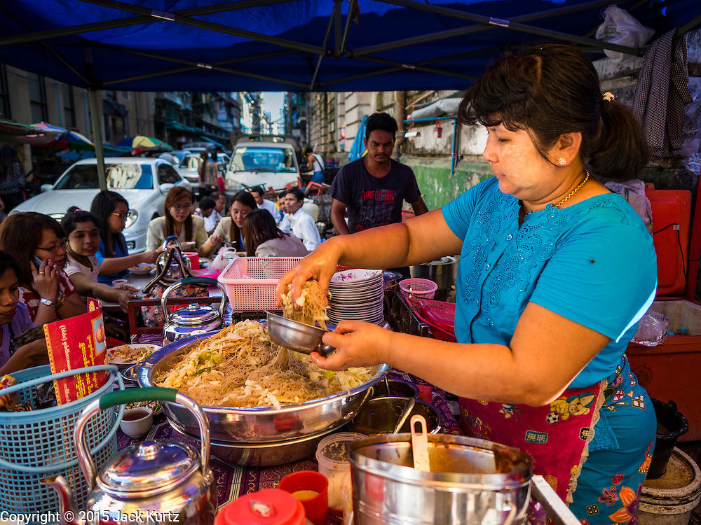 """06 NOVEMBER 2015 - YANGON, MYANMAR: A woman makes a batch of noodles for a customer at her street food stall in Yangon. Some economists think Myanmar's informal economy is larger than the formal economy. Many people are self employed in cash only businesses like street food, occasional labor and day work, selling betel, or working out of portable street stalls, doing things like luggage repair. Despite reforms in Myanmar and the expansion of the economy, most people live on the informal economy. During a press conference this week, Burmese opposition leader Aung San Suu Kyi said, """"a great majority of our people remain as poor as ever.""""   PHOTO BY JACK KURTZ"""