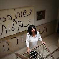"""Peggy Cidor, a leading woman of the Women of the Wall organization, stand in the hallway of her building in Jerusalem, Monday, May 20, 2013. The grafitti reads"""" The women of the Western Wall are despised"""". The group, known as """"Women of the Wall,"""" convenes monthly prayer services at the Western Wall, the holiest site where Jews can pray, wearing prayer shawls and performing rituals that ultra-Orthodox Jews believe only men are allowed to do...Israeli officials initially opposed the group but have recently backed its right to worship. Earlier this month, thousands of ultra-Orthodox protesters tried to prevent their prayer service"""