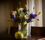 A vase of purple, white, and green flowers, arranged on a kitchen table with a fresh quince