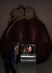 © Licensed to London News Pictures. 03/03/2016. A woman views a pair of boxing gloves worn by Muhammad Ali when he fought Henry Cooper in 1963 at the I Am The Greatest  - Muhammad Ali Exhibition press preview. Exhibition featuring more than 100 artefacts from the boxer's career, put together with the help of the Ali family, showcased to celebrate the life of the former heavyweight champion giving an insight into one of the sport's most famous personalities. London, UK. Photo credit: Ray Tang/LNP
