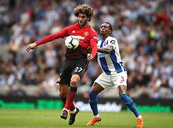 Manchester United's Marouane Fellaini (left) and Brighton & Hove Albion's Gaetan Bong battle for the ball