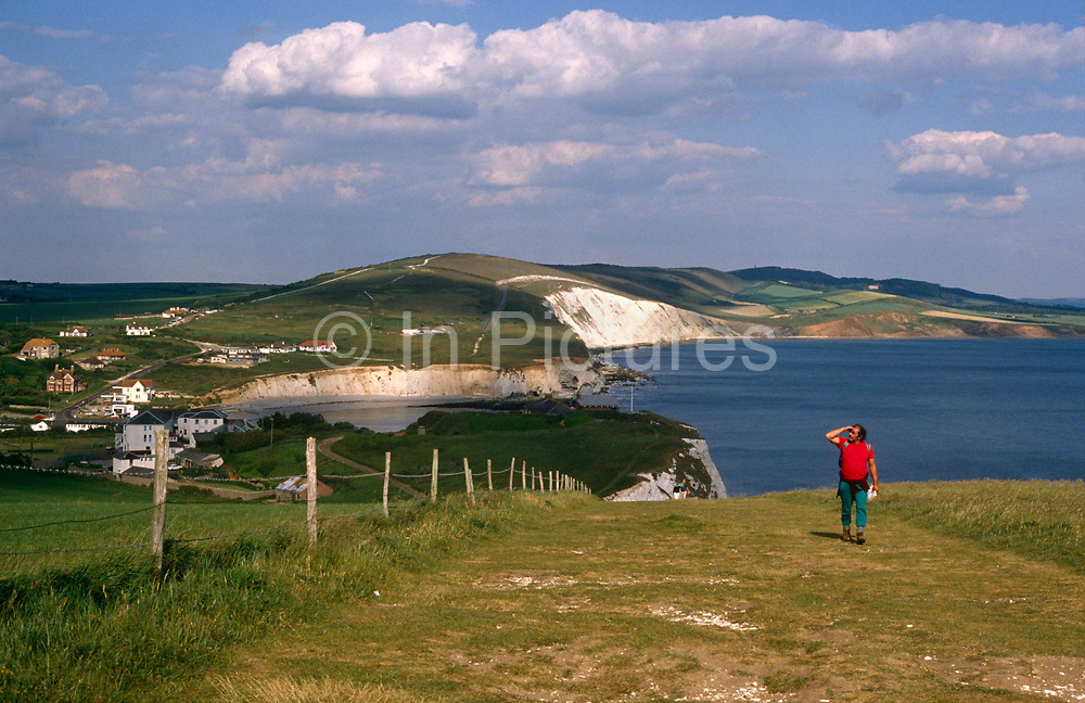 A walker admires the view across the escarpment of Tennyson Downs on the Isle-of-Wight. Looking over his shoulder into the distance, the walker is alone on his solo pursuit along some of Britain's most beautiful coastlines, here on the south coast. The rolling downland stretches westwards - its white chalk cliffs famous for symbolising England's southern limits. Tennyson Down is a hill at the west end of the Isle of Wight just south of Totland. Tennyson Down is a grassy, whale-backed ridge of chalk which rises to 482 ft/147m above sea level. Tennyson Down is named after the poet Lord Tennyson who lived at nearby Farringford House for nearly 40 years. The poet used to walk on the down almost every day, saying that the air was worth 'sixpence a pint'.