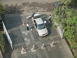 Security guards with sniffer dog and mirror for looking under vehicles check car coming into the Grand Hyatt hotel, Mumbai.