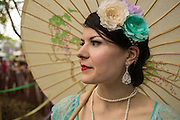 A woman wearing a floral headpiece shades herself with a parasol at the Jazz Age Lawn Party.