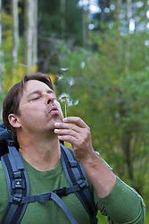 hiker blowing a milkweed