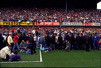 A Liverpool Fans spill onto the pitch and also climb to the above stand for safety<br />